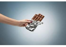 拿着一块巧克力的女人的手_6641172