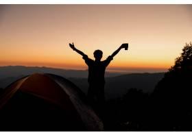 拿着咖啡杯的快乐男子的剪影在山上的帐篷附_4351616