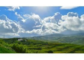 多云的天空下有许多山脉的美丽的绿色景观_9761054