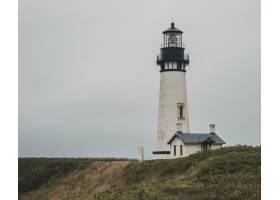 山顶上一座房子附近的黑白相间的灯塔的宽阔_8409350