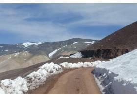 在明亮的天空下美丽的山区景观部分被白雪_13061823