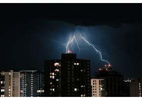 夜晚城市中建筑物上空黑暗天空中的闪电_10399144