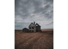 在灰色天空下的大片棕地里一座废弃的被_7810320