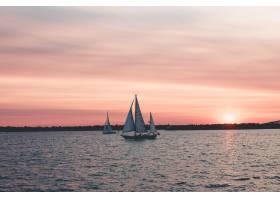 在粉色天空下拍摄的海上帆船的美丽风景_7848672