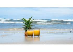 在美丽的海滩上喝新鲜的夏日菠萝饮料_9434993