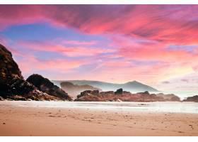 在美丽的粉色日落期间多云天空下被岩石和_11301420