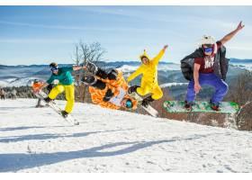 在群山的衬托下男子们在他的滑雪板上跳跃_7927114