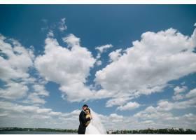 在蓝天碧水的背景下美丽的新人结婚_10629316