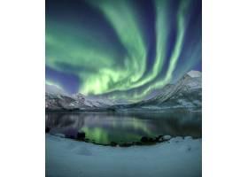 天空中美丽的北极光下白雪覆盖的山脉的垂直_9076807