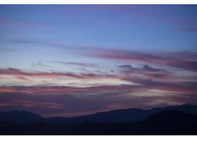 太阳落在暗色背景上的积云日落云_5445631
