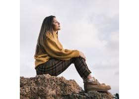 坐在岩石上的年轻女子在天空的衬托下享受大_4440758