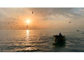 坐在阳光灿烂的美丽大海中央的一只小划艇上_7814883