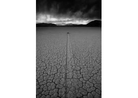 垂直灰度拍摄的被山区风景包围的荒芜沙地_9759697