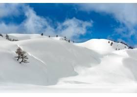 在多云的蓝天中被白雪覆盖的山丘的风景照片_10399735