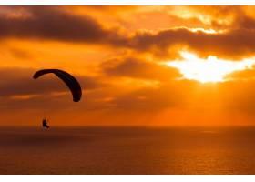 在日落时分滑翔伞令人惊叹的多云天空和阳_7631056