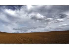 在乌云密布的灰色天空下的棕色沙地_11890817