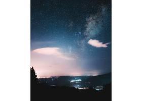 午夜开始的美丽天空下树木的剪影_7810463