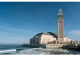 哈桑二世清真寺在蓝天和阳光下被水和建筑物_11942290