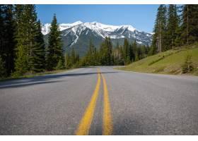 低角度拍摄一条被森林和雪山包围的高速公路_9184232