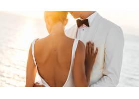 傍晚的阳光照耀着美丽的新婚夫妇他们在海_3985001