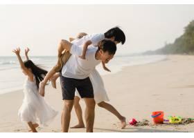 亚洲年轻幸福的一家人晚上在海滩上享受假期_7685875