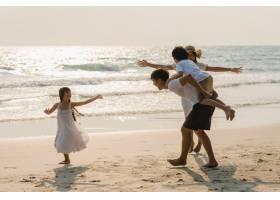 亚洲年轻幸福的一家人晚上在海滩上享受假期_7685876