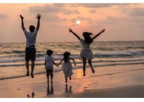 亚洲年轻快乐的一家人晚上在海滩上享受假期_7685881