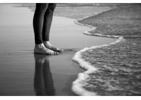 人体赤脚站在沙滩上的灰度照片_11301347