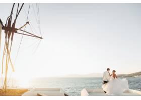 从远处看可爱的新婚夫妇看着海面上的日落_3984994
