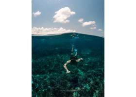 以天空为背景的男子在水下游泳的垂直镜头_7753639