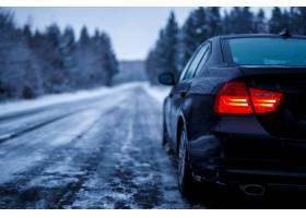 一辆黑色的汽车在结冰的道路上行驶周围是_12908900