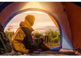 一个年轻人拿着咖啡杯坐在帐篷里_4351618
