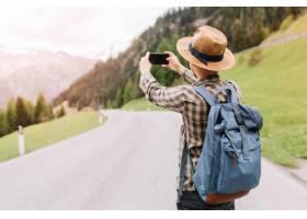 一位穿着时髦格子衬衫的男性旅行者拍摄了一_10561747