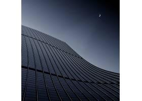一座现代商业建筑触及晴朗天空的低角拍摄_9852531