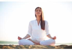 一名女子在海滩上做瑜伽练习_859036