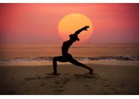 一名女子背着太阳练习瑜伽_999864