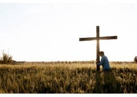 一名男子在草地上用头靠在木制十字架上的美_9283361