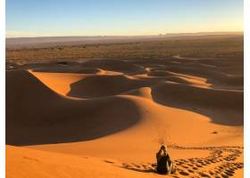 一名男子坐在被铁轨包围的沙漠中的太阳沙丘_13061664