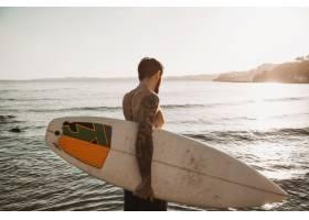 一名男子拿着冲浪板站在海滩上_3648809