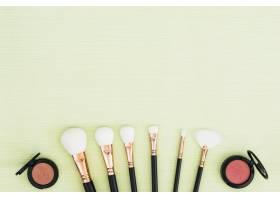 薄荷绿色背景上的白色化妆刷和粉色致密粉末_4441194