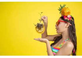 身穿泳衣的美女拿着蜂窝摆出黄色的姿势_5219550