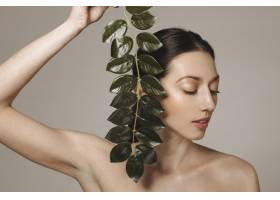 深色头发的女孩拿着异国情调的叶子摆姿势_4606967