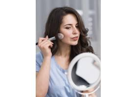 漂亮的黑发女子用刷子和镜子化妆_4351493