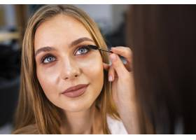 特写化妆师在女性身上涂睫毛膏_5863575