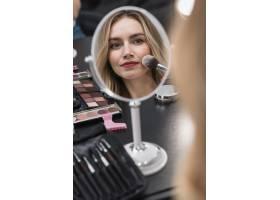 一位年轻的金发女子使用化妆品的肖像_4351499