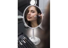 一位年轻的黑发女子涂抹化妆品的肖像_4351497