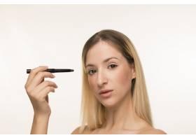 一名金发女子在脸部附近画着眼线_5263753