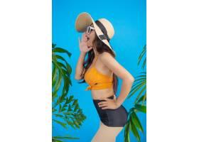 一位身着泳装的美女在蓝色上摆出一个手势_5219562