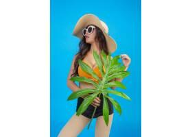 一位身穿泳衣手持绿叶的美女在蓝色上摆姿_5219564