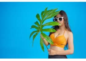 一位身穿泳衣手持绿叶的美女在蓝色上摆姿_5219565
